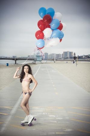 Beautiful model wearing the United States flag bikini on skates holding USA color ballons at the beach sidewalk photo