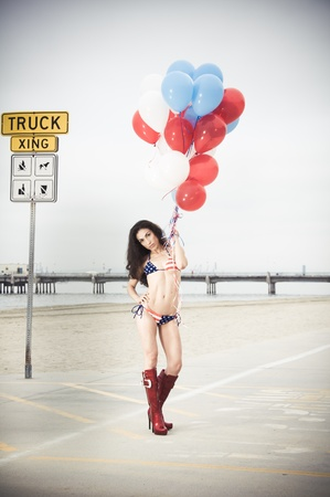 Beautiful model wearing the United States flag bikini on skates holding USA color ballons at the beach sidewalk photo