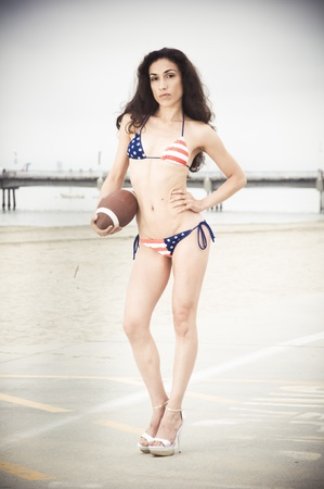 Beautiful model wearing the United States flag bikini on skates holding USA soccer ball at the beach sidewalk photo