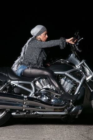 Beautiful biker model posing with motorcycle wearing a trendy fashion outift Stock Photo