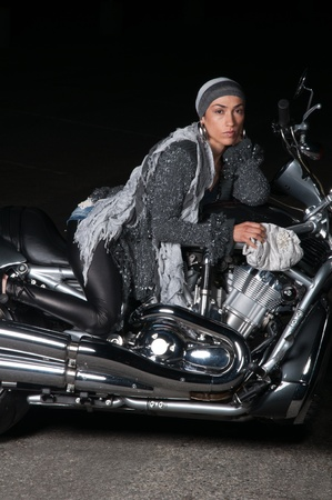 Beautiful biker model posing with motorcycle wearing a trendy fashion outift photo