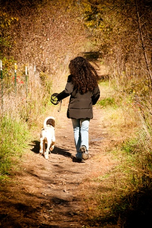 Curly hair woman running in the forest green with her puppy dog photo