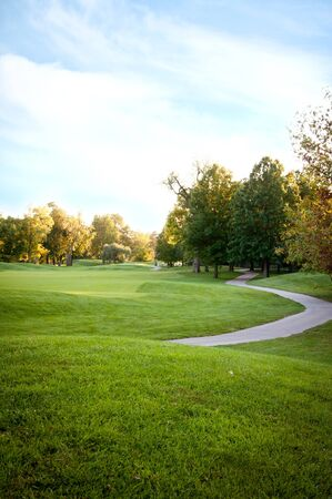 fairway: Bright green golf course sorrounded by beautiful trees Stock Photo