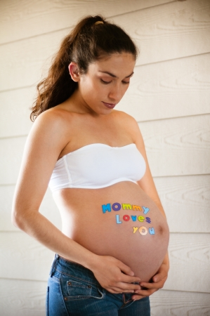 Beautiful pregnant model expecting newborn wearing jeans and white top photo