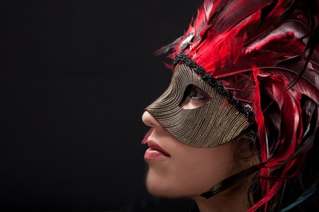 Mooi model draagt een veertje masker symboliseert mardi gras of Venetiaanse carnaval