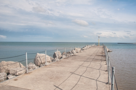 Ocean side beach pier under brigh blue sky photo