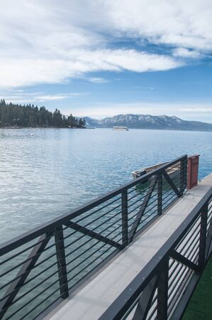 Beautiful Lake Tahoe shore overseeing the snowy mountains and bright blue sky photo