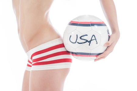 Beautiful model wearing blue,  red and white underwear holding a USA team ball isolated on white representing a football or soccer cheerleader