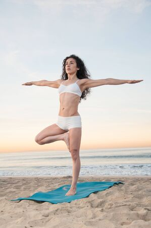 energizing: Beautiful athletic woman praticing energizing and relaxing yoga exercises on a colorful sunrise on the beach