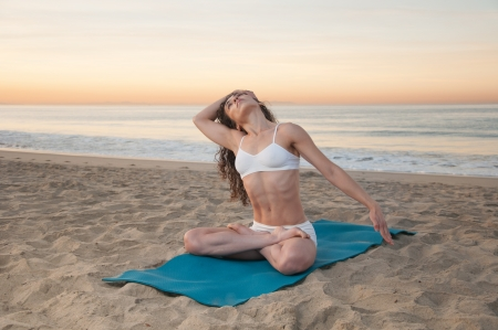Beautiful athletic woman praticing energizing and relaxing yoga exercises on a colorful sunrise on the beach