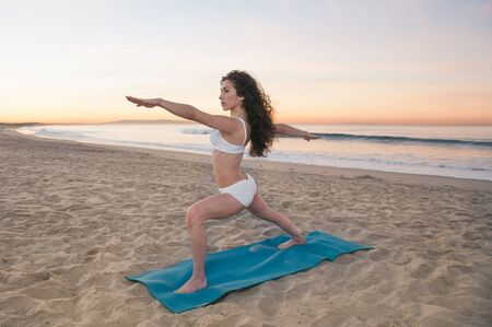 Beautiful athletic woman praticing energizing and relaxing yoga exercises on a colorful sunrise on the beach photo