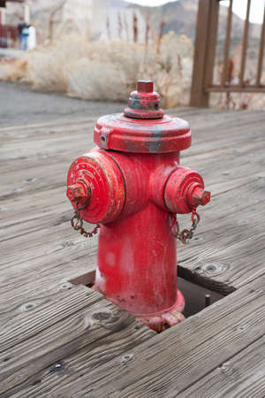 Old style bright red fire hydrant on historic city wood sidewalk photo