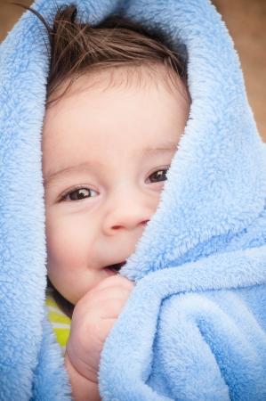 Baby boy under light blue blanket after a bath