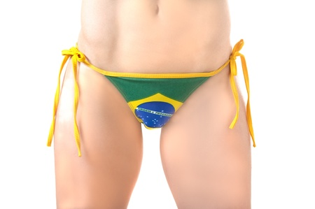 Beautiful Brazilian cheerleader model wearing a green and yellow soccer flag thong bikini bottom isolated over white background photo