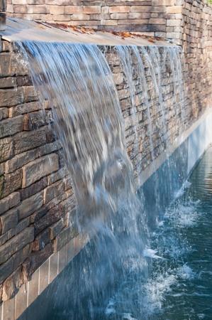 Brick stone waterfall on luxury backyard pool during summer time Stock Photo