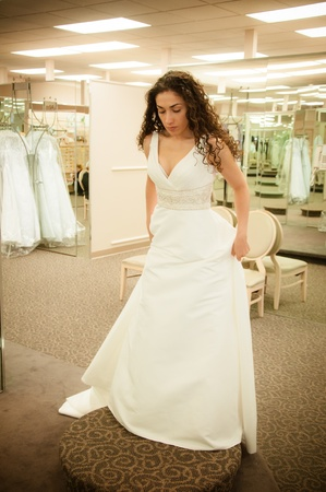 Beautiful woman trying a white bridal wedding dress before getting married