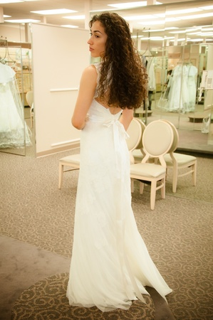 Beautiful woman trying a white bridal wedding dress before getting married photo