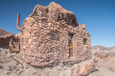 Old West Mining Shack in the California Desert under a bright blue sky photo