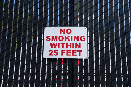 Red no smoking within 25 feet sign on black fence photo