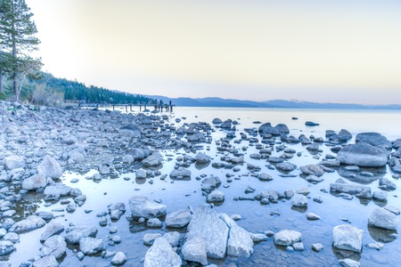 Lake Tahoe rocks over the water shore on a beautiful sunrise on the mountains photo
