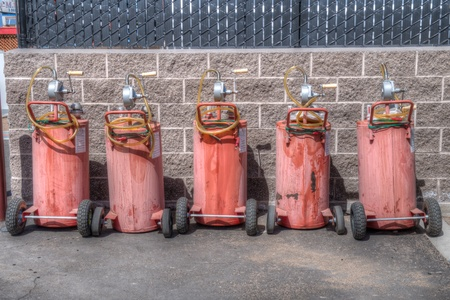 Five red portable gas pumps resdy to be used to fill boats gas tanks photo