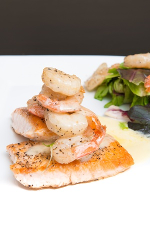 Grilled salmon topped with a creamy white sauce served with spring greens and shrimp photo