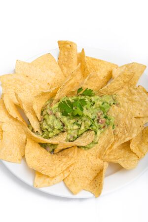 totopos: Green spicy guaccamole served with corn tortilla chips over white background Stock Photo
