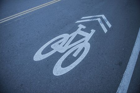 Bike lane route sign in blue and white painted on asphalt photo