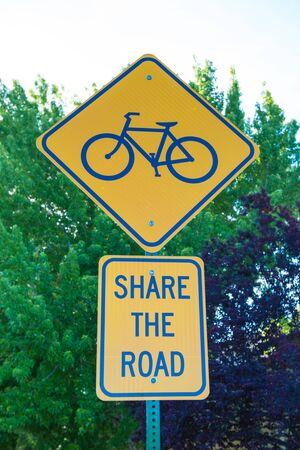 Bike lane route sign in blue and white surrounded by nature green photo