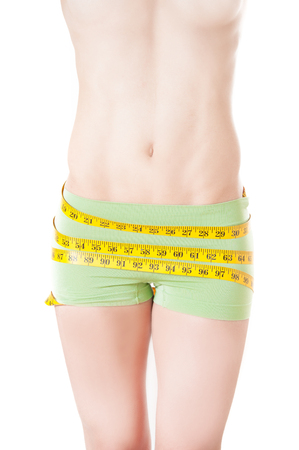Model wearing workout shorts measuring belly with yellow tape isolated over white background photo