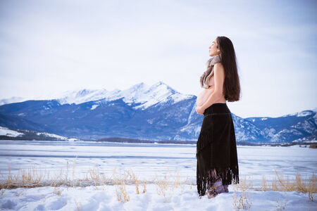 Beautiful expecting mother to be pregnant woman posing in front of nature in a winter wonderland snowscape at a lake by the mountains photo