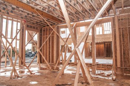 wooden joists: Unfinished house construction frame under rain Stock Photo