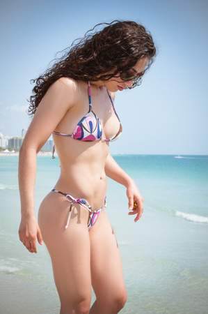 Beautiful fit model wearing a thong bikini at the gorgeous blue water beaches of florida on vacation Stock Photo