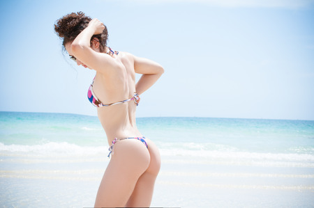Beautiful fit model wearing a thong bikini at the gorgeous blue water beaches of florida on vacation photo