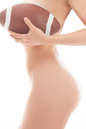 Beautiful woman nude holding a football isolated over white background