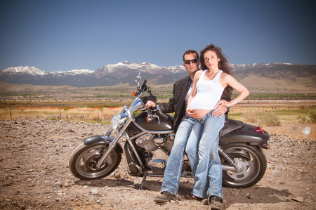 Man and woman couple expecting child posing nest to motorcycle representing a biker family