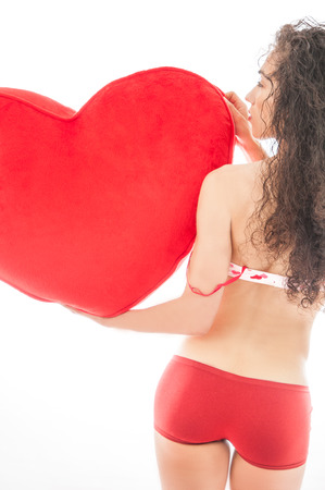 Beautiful model wearing pink and red underwear holding a heart pillow symbolizing a valentines day gift