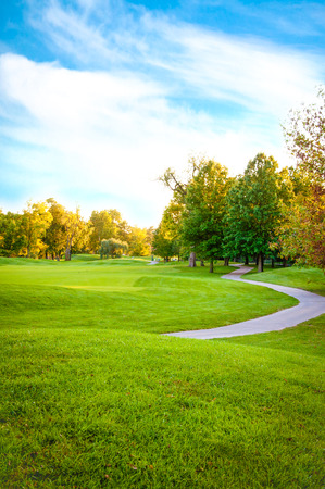 Bright green golf course sorrounded by beautiful trees Stok Fotoğraf