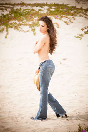 Woman wearing jeans topless on the beach with flowers on the background