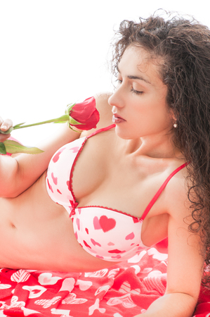 Beautiful model wearing pink and red underwear holding a red rose symbolizing a valentines day gift Stock Photo
