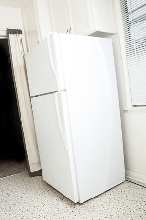 Simple white refirgerator and freezer on corner of kitchen photo