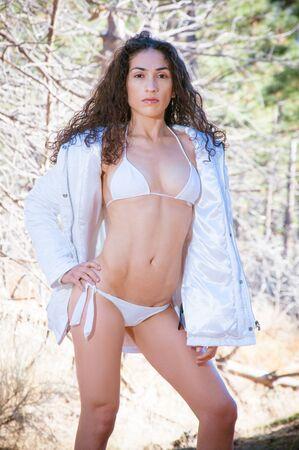Beautiful model wearing a white thong bikini on a winter snowy landscape background Stock Photo