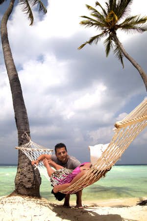 Woman relaxing in a hammock strung between palm trees on a tropical beach chatting to a handsome young man photo