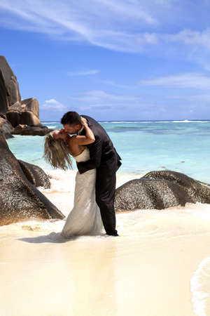Romantic bridal couple enjoying a passionate kiss on a tropical beach with ocean backdrop photo
