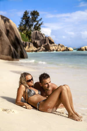 Romantic young couple lying on the beach in the sand enjoying the summer sunshine photo