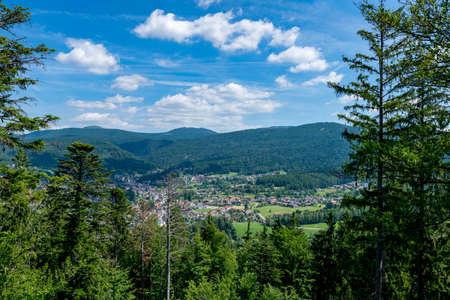 View from top of a mountain with rocks and stones and much clouds on the sky on a sunny day in the bavarian forest