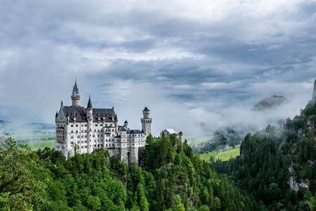 Castel called Neuschwanstein in bavaria with clouds on the sky and a little fog on a sunny day Reklamní fotografie