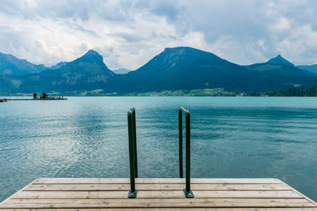 footbridge with a pool ladder in the lake in Austria which wolfgangsee is called with mountains in the background