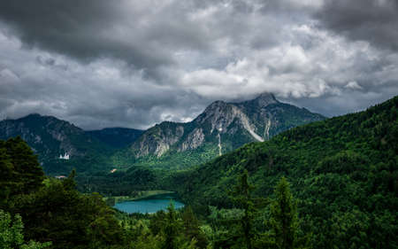 View from top of a mountain in the landscape with clouds on the sky in bavaria with a lake in the middle