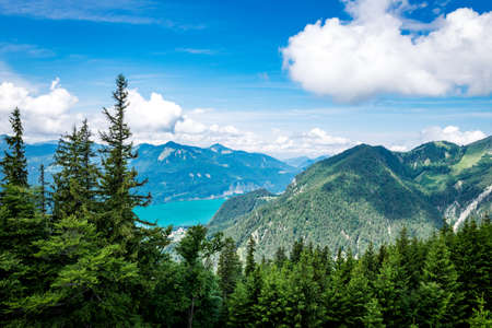 View from a top of a mountain to a lake called Wolfgangsee in Austria with mountains on the background and clouds on the sky and trees in front of